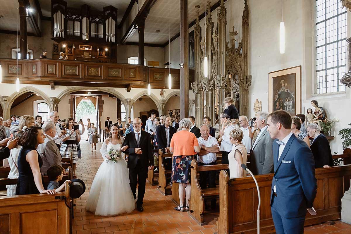 La mariée entre au bras de son papa sous le regard de son jeune mari-photographe-mariage-alsace