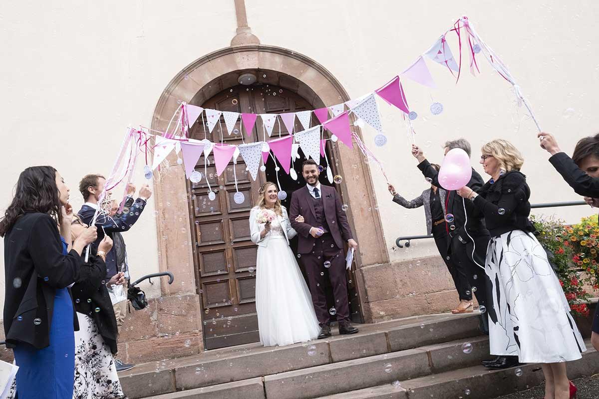 Sortie de l'église sous les bulles et les applaudissements-photographe-mariage-alsace