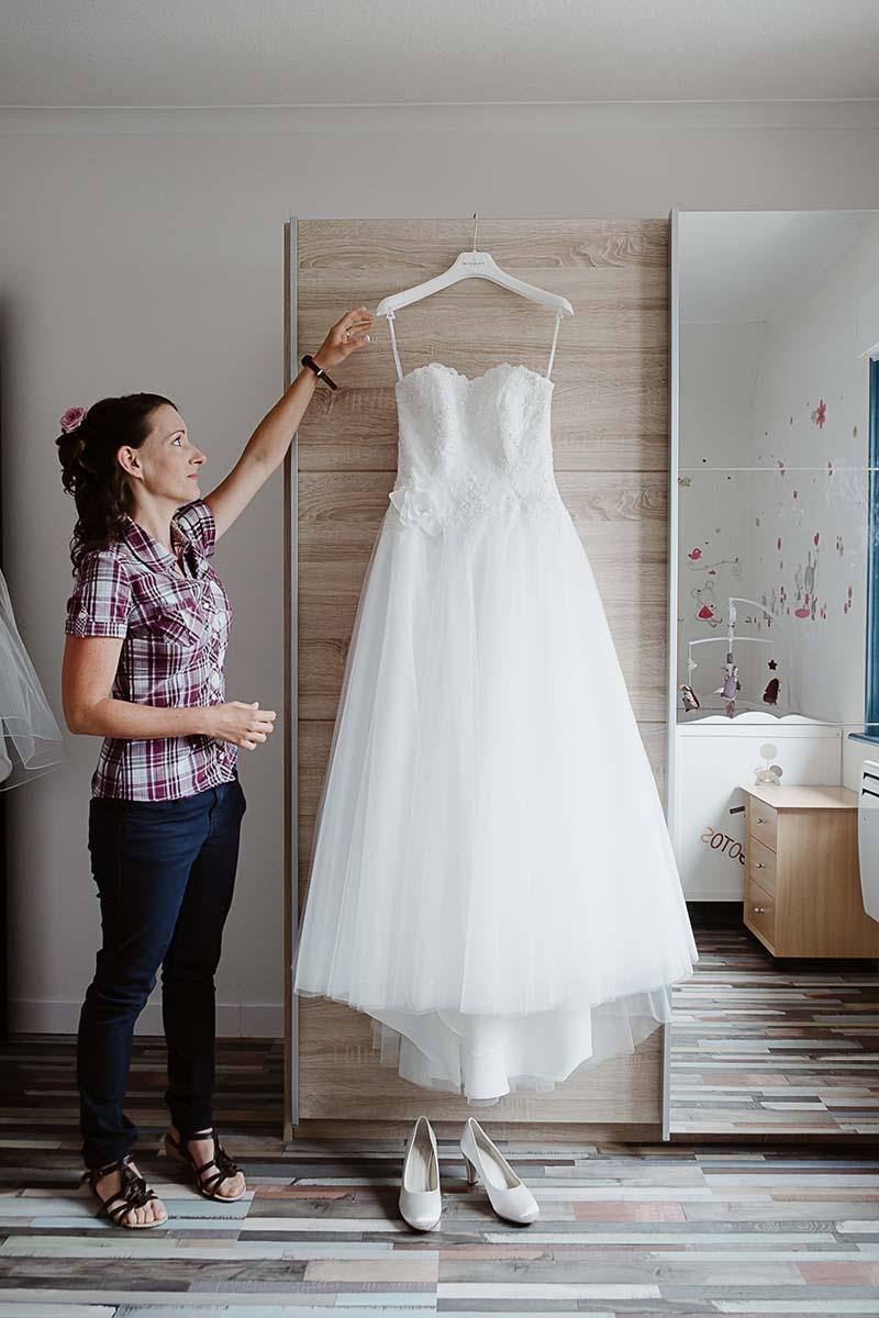 La mariée décroche sa robe dans la chambre de sa fille-photographe-mariage-alsace