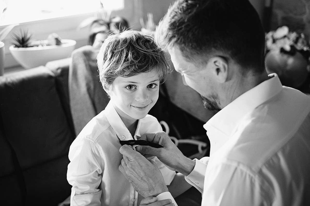 le marié habille son fils lors des préparatifs du mariage