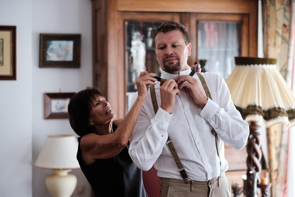 La mère du marié aide son fils à s'habiller-photographe-mariage-alsace